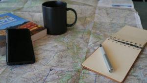 Planung mit Landkarte, Wanderführer, Notizblock und Stift
