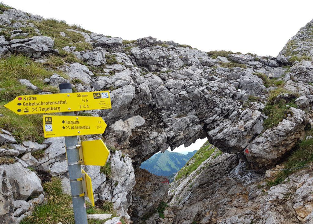 Loch im Fels, genannt Fensterl, mit Wegweisern davor