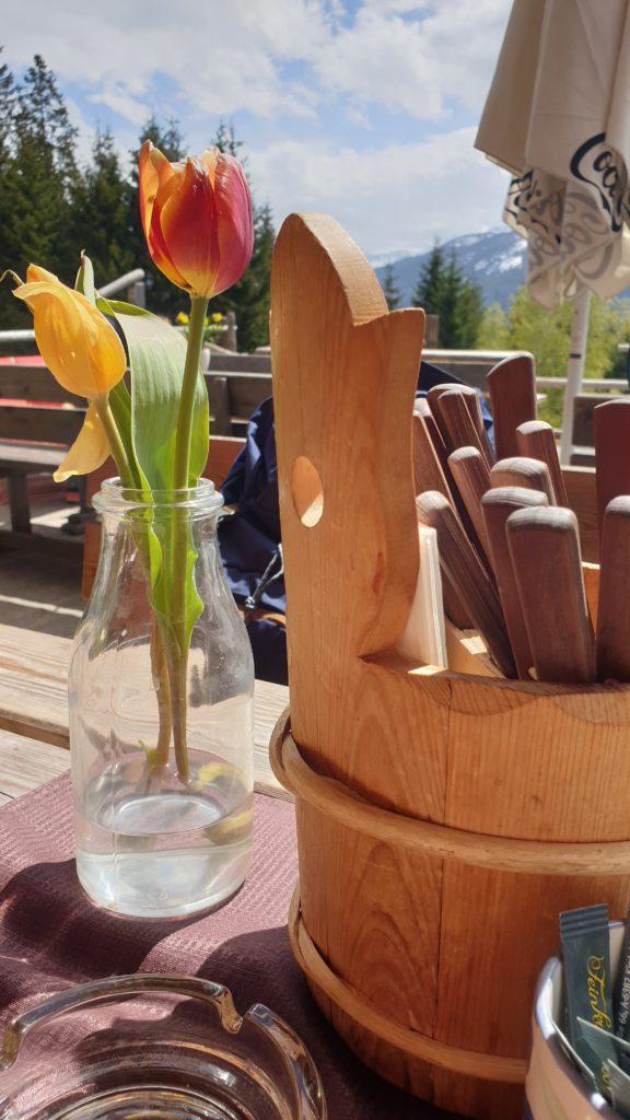 Pause an der Bürgerbergalm mit Blumen auf dem Tisch