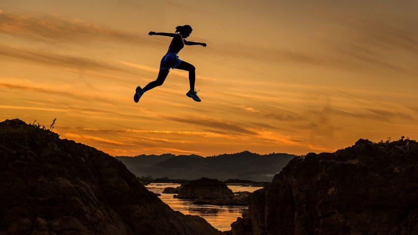 Springende Frau vor Bergen