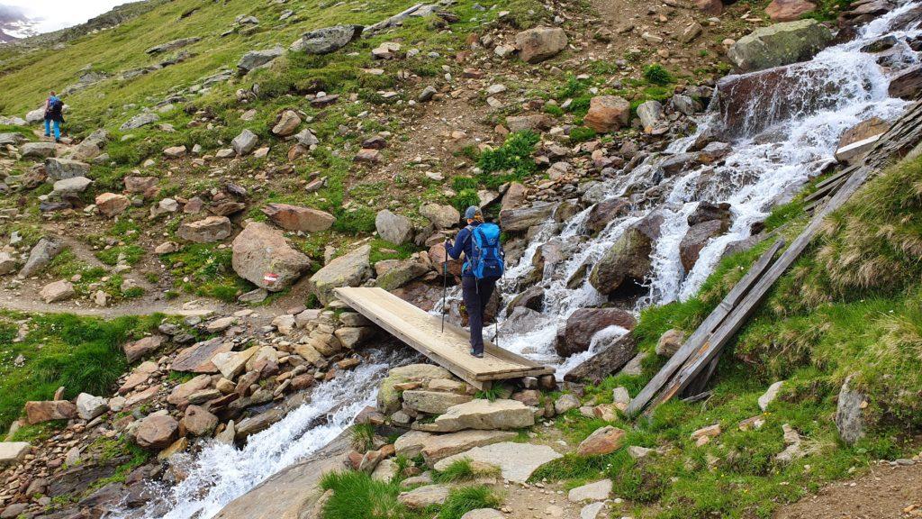 Querung eines größeren Gebirgsbaches über eine Holzbrücke